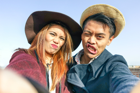 Hipster asian couple making selfie with funny faces - Lovers having fun together outdoor - Technology and fashion lifestyle concept - Soft brown vintage filtered look