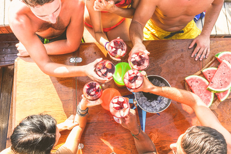 Happy friends having fun outdoors in boat party - Young people enjoying summer vacation together toasting wine with fruit - Youth and friendship concept - Main focus on top hand red wine glass Фото со стока