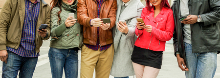 Happy multi ethnic friends watching smart mobile phones - Young diverse culture people chatting with cellphones - Technology trend addiction concept - Focus on two left guys hands - Warm filter