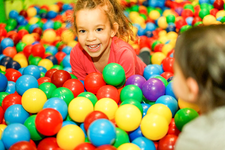 pool rooms: Cheerful children playing inside ball pit swimming pool - Happy people having fun in baby playground indoor - Childhood and friendship concept - Soft focus on left female face - Warm vivid filter