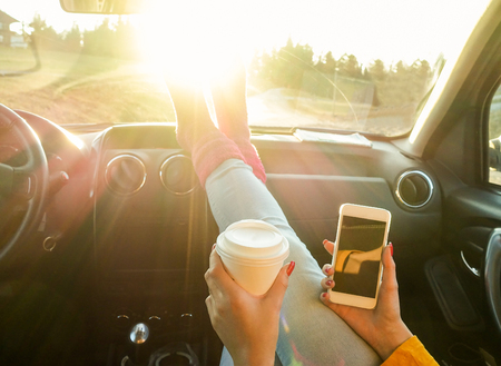 Woman toasting coffee take away go cup and using smart phone inside car with feet in warm socks on dashboard - Travel and trend concept - Focus on paper cup hand - Warm filter with original sun light Stock Photo