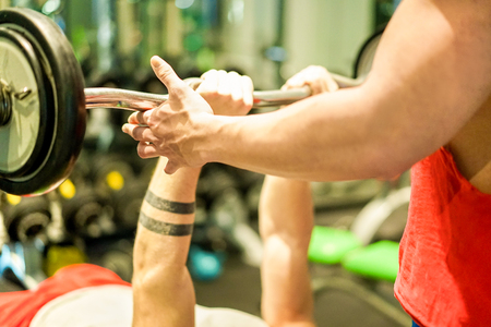 Athlete training with barbells inside american gym club with personal coach - Young man doing strength workout - Healthy lifestyle and bodybuilding concept - Focus on right man hand - Warm filter