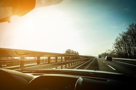 Vue de la fenêtre de voiture des camions accélérant dans l'autoroute avec la lumière du soleil arrière - Véhicules à déplacement rapide au coucher du soleil - Concept de transport - Focus sur les semi-remorques et la voiture - Filtre chaud avec édition de vignette