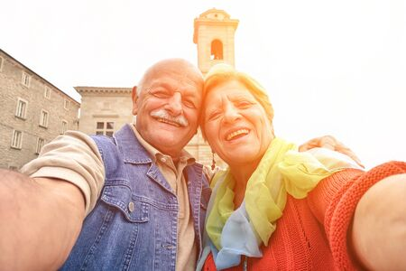 Senior couple taking a selfie in old town center - Two persons in the 60s having fun with new technologies outdoor at sunset - Concept of active elderly and fun around the world Фото со стока