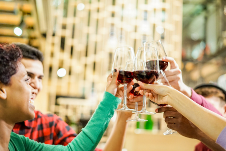 Group of multiracial friends cheering with red wine at pub cocktail bar - Young people toasting aperitif drinks in restaurant - Friendship and party concept - Soft focus on right bottom hand glass
