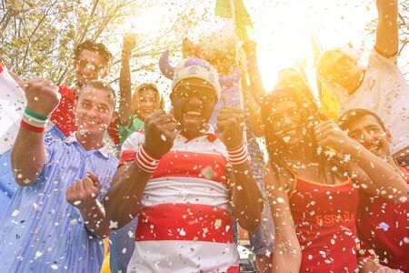 Multinational football supporters celebrating a goal in bar restaurant outdoors - Happy multiracial people having fun for olympic games - Sport against racism concept - Soft warm filter Stock Photo