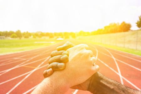 Corredores multirraciales estrechar la mano antes de la competencia atlética con la iluminación de la espalda - Personas multiétnicas que muestran respeto contra el racismo - Concepto de competencia justa - Soft warm filter