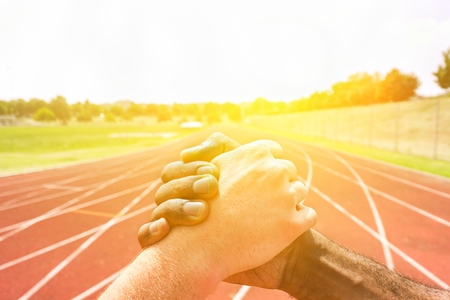 Multiracial runners shaking hands before athletic competition with back lighting - Multi-ethnic people showing respect against racism - Fair competition concept - Soft warm filter Stock Photo