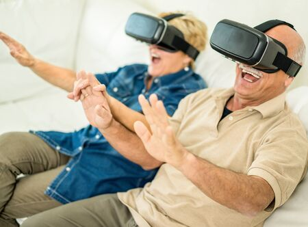 Senior mature couple having fun with virtual reality glasses - Old people using new vr headset - Concept of active elderly and interaction with new technologies - Focus on man goggles - Warm filter
