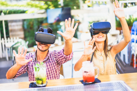 Amazed friends looking in VR goggles and gesturing with hands in cocktail bar restaurant - Young people having fun with new phone trends - Technology concept - Soft focus on man - Warm vivid filter Stock Photo