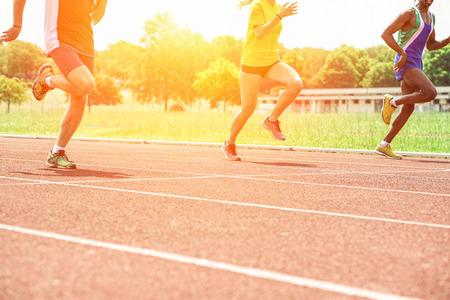 Atletas multiétnico corriendo en atletismo pista al atardecer - Tres corredores de sprinting para el entrenamiento con la iluminación de la espalda - Competición deportiva y concepto de estilo de vida saludable - Suave enfoque en la pierna izquierda