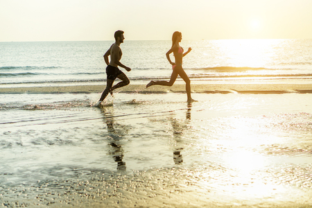 Silhouette of young happy couple running on seashore splashing water with back sun light - Two cheerful lovers having fun on the beach - Love and vacation concept - Soft focus on him - Warm filter Stock Photo