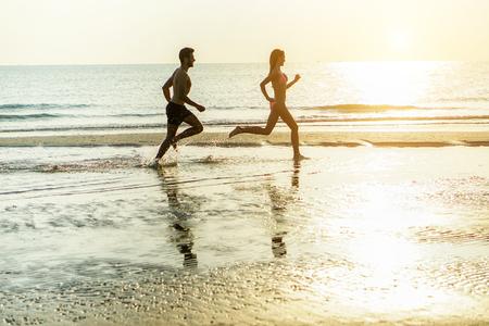 Silueta mladého šťastného páru, který běží na pobřeží, stříkající vodu se slunečním zářením - Dva veselí milenci se baví na pláži - Láska a dovolená - Měkké zaměření na něj - Teplý filtr