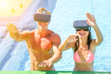 Young happy couple wearing virtual reality headset in swimming pool during summer vacation - Cheerful friends having fun together - Concept of new technology trends addiction - Main focus on man