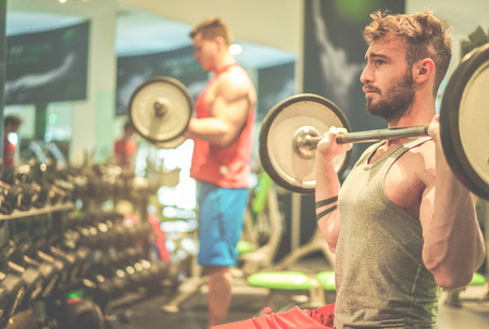 Athletes friends training with barbells inside american gym club - Young people doing strength workout - Healthy lifestyle and bodybuilding concept - Focus on right man face - Cinematic filter