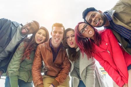 Happy friends taking selfie photo making funny faces with back sun light - Young multiracial people having fun together outdoor - Multi race friendship concept - Focus on two right guys - Warm filter Stock Photo