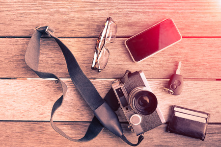 Outfit of traveler, photographer, student, teenager, young man - Overhead of essentials for modern young person - Old and New concept with wood texture - Warm vintage filter look Reklamní fotografie