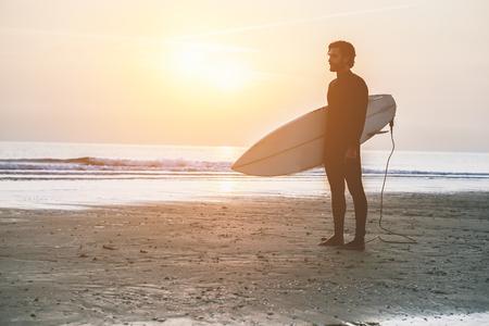 Silhouette de surfeur debout sur la plage en attente de vagues au coucher du soleil - Homme avec la planche de surf vêtu d'un costume humide regardant le lever du soleil - Concept de sport extrême - Soft focus sur l'homme - Edition vintage
