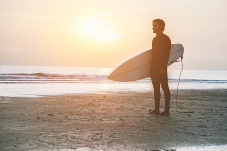 Silhouette of surfer standing on the beach waiting for waves at sunset time - Man with surfboard wearing wet suit looking sunrise - Extreme sport concept - Soft focus on man - Vintage editing