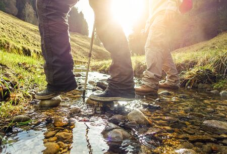 Two friends doing trekking in switzerland mountains in summer time with back sun light - Sporty hiker people crossing brook in sunny day - Healthy lifestyle concept - Focus on left feet - Warm filter