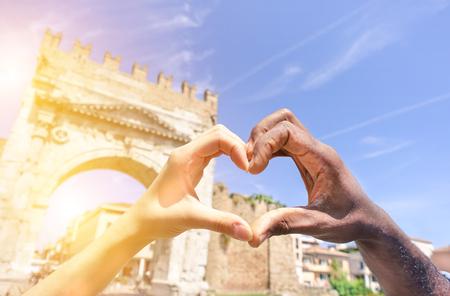 낭만적 인 휴가 - 젊은 multiracial 부부 만들기 사랑 기호 다음 심장 모양을 게재하는 여자와 남자 손의 근접 촬영 로마 기념물 - 다중 민족 관계 개념 - 초