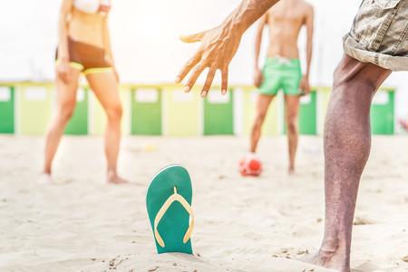 Multi závodní přátelé hrají fotbal na pláži - Mladí lidé mají sportovní rekreace v letní čas - Guy střílí na gól - Dovednostní koncept - Měkké zaměření na flip flop - Teplý filtr