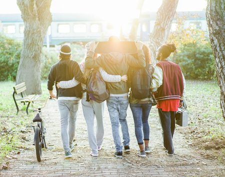 Group of friends walking in city park with train and sun light in background - Young people having fun in university break - Leisure after school concept - Soft focus on center heads - Warm filter
