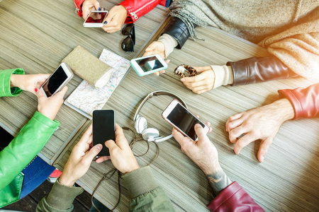 Group of friends are addicted using mobile phone devices - Upper point of view people hands using smart cell phones together - Technology and teamwork concept - Focus on bottom hands - Warm filter