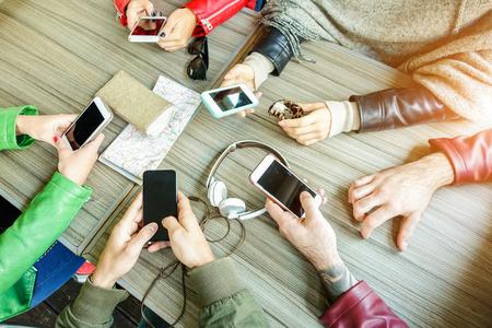 Skupina přátel je závislá na zařízeních s mobilním telefonem - Horní pohled na lidské ruce pomocí inteligentních mobilních telefonů dohromady - Technologie a koncepce týmové práce - Zaměřte se na spodní ruce - Teplý filtr
