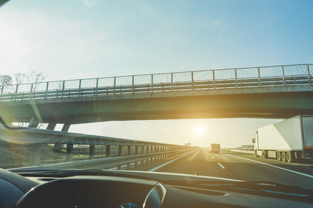 Vista de la ventana del coche de los camiones de exceso de velocidad en la autopista en virtud de un puente superior con la luz de fondo - vehículos de movimiento rápido en la puesta del sol - concepto de transporte - centrarse en semitrucks - Foto de archivo