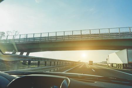 Vue de la fenêtre de voiture des camions qui accélèrent en autoroute sous un pont de dépassement avec rétro-éclairage - Véhicules à déplacement rapide au coucher du soleil - Concept de transport - Focus sur semi-remorques - Filtre brut vintage