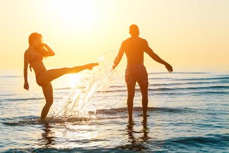 Silueta de la feliz pareja nadando y jugando en el agua al atardecer en la playa - Los jóvenes que se divierten en el tiempo de verano - Las vacaciones y el amor concepto - Suave enfoque en él - Sun color original
