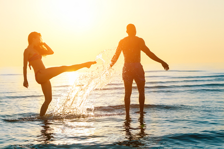 Sylwetka szczęśliwej pary pływanie i grając w wodzie o zachodzie słońca na plaży - Młodzi ludzie zabawy na letni czas - koncepcja urlopu i miłości - nieostrość na niego - niedz oryginalny kolor Zdjęcie Seryjne