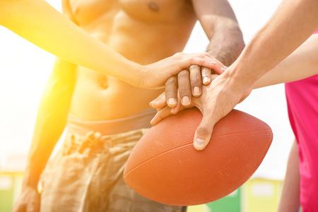 Multirracial amigos jugando rugby en la playa en día soleado - Multinacional manos en la parte superior de la bola oval - Verano deporte contra el racismo concepto - Sunshine tonos de color suave con filte caliente