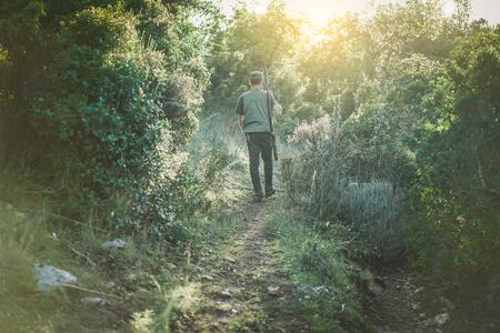 Jeune homme qui chasse en automne avec l'éclairage arrière - Hunter marche dans un sentier dans le bois - Concept de chasse et de loisir - Facile à mettre sur lui - Filtre brut chaud avec un flambeau de halo au fond Banque d'images