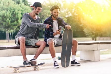 젊은 skaters 다시 조명 - 스마트 트렌드와 함께 자유 시간을 공유하는 가장 친한 친구 스마트 폰 기술로 중독 개념 - 오른쪽 남자에 대 한 소프트 포커스  스톡 콘텐츠