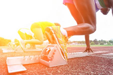 Běžecké nohy na startovních blocích v atletické běžecké dráze - mladí multi závodníci vycvičení venku při západu slunce - zblízka na botu s podsvícením - měkký teplý filtr s měkkým zaměřením na první boty