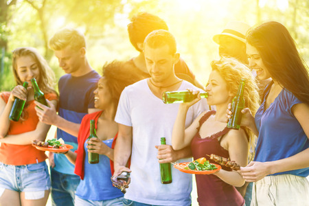 Group of multi-ethnic friends having barbecue meal outdoor on park with back lighting - Young cheerful people enjoying bbq on summer time - Friendship concept - Soft focus on right girl