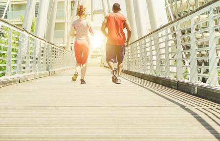 Dva mladí sportovci dělají jogging v městské soutěži oblasti venkovní - Běžecké školení venkovní - Běh pro sportovní koncept zdravého životního stylu - Hlavní zaměření na levé boty - Měkký teplý hnědý filtr