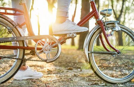 Young woman on old style italian bicycle with back light - Close up of girl feet riding vintage bike in park outdoor for fall time - Vintage fashion concept - Focus on top foot - Warm retro filter