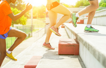 ランナーの背中太陽テラス階段のスタジアムでトレーニング - 若い選手が大学の競争のための準備 - 健康的なライフ スタイルを光し、スポーツの概