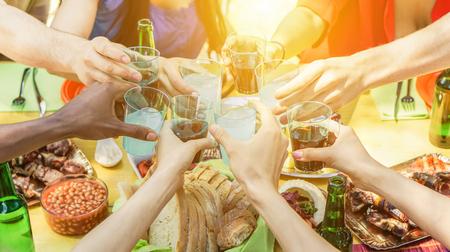 Groep vrienden die met aperitief roosteren die barbecue openlucht eten - Close-up van handen die met cocktails en bieren toejuichen - Vriendschap, de zomer, pret en dinerconcept - Zachte nadruk op juiste bodemhand Stockfoto