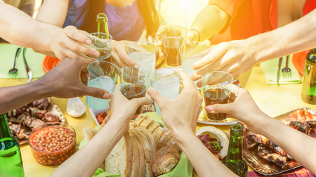 Group of friends toasting with aperitif eating barbecue outdoor - Closeup of hands cheering with cocktails and beers - Friendship,summer,fun and dinner concept - Soft focus on right bottom hand Stock Photo