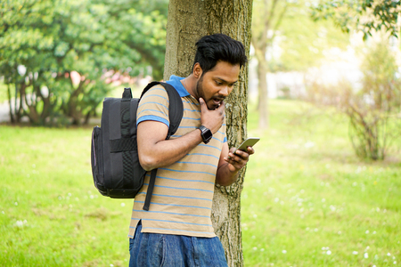 University indian student using mobile phone outdoor Portrait of a young Indian man texting in park residential contest - New technology trend addiction concept - Warm vivid filter with sun flare Stock Photo