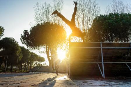 Los amigos que realizan freestyle biking y breakdancing al mismo tiempo - break bailarín y ciclista de formación al aire libre en el parque de la ciudad - concepto de deporte extremo - enfoque suave en el derecho parkour silueta cabeza del hombre Foto de archivo