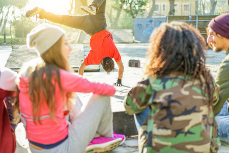 Happy friends listening music in skateboard city park with man breakdancing - Young hip hop style people having fun outdoor - Friendship concept - Soft focus on breakdancer - Warm filter with sunlight