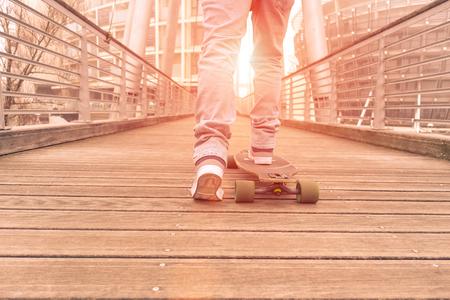 Hipster guy en action sur le pont en bois - Skater garçon conduisant au coucher du soleil autour de la ville - Concept de sport et de loisirs dans le concours urbain - Filtre vintage brun doux avec lumière solaire artificielle Banque d'images