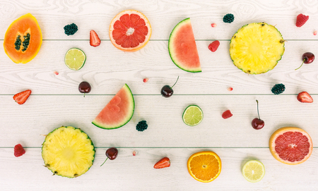 Minimal composition of tropical and european fruits - Mix of summer colored fruits on wood background - Healthy lifestyle concept - Soft saturated filter with main focus in the middle of the frame Foto de archivo