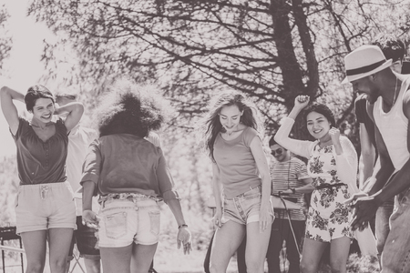 feasting: Happy friends dancing with dj set in outdoor party - Young multi ethnic people having fun listen music - Black and white editing - Focus on two right girls - Warm matte effect Stock Photo