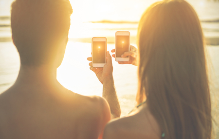 Silhouette of young couple shooting together beautiful sunset with smart cell phone on the beach - Two lovers enjoying summer vacation - Love concept - Focus on smartphones - Warm cinematic filter